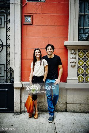 Portrait of smiling couple leaning against building holding flowers on sidewalk of city street