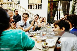 Smiling family clapping for grandfather during family dinner party in restaurant
