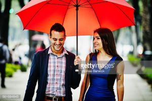 Smiling couple in discussion walking under umbrella on sidewalk of city street