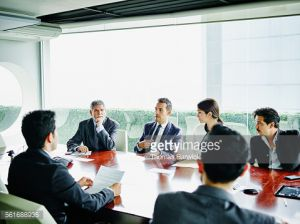 Male business executive leading team meeting with colleagues in office conference room