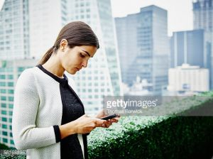 Businesswoman working on smartphone on office terrace overlooking cityscape