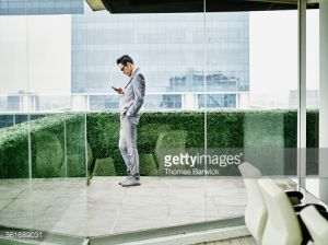 Businessman standing on office terrace working on smartphone