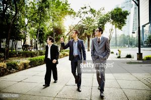 Three businessmen in discussion walking on sidewalk in city