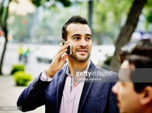 Businessman talking on smartphone on sidewalk of city street